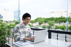 Asian young business man working with laptop at the city cafe. Stock Images