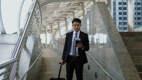 Asian young businessman with baggage and looking paper map in ha. Asian young businessman walks along the baggage with haste, and reading the paper map in hand Royalty Free Stock Photography