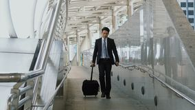 The colleagues walking dragging luggage passed in haste. The Asian young businessman drag a black baggage down the slope with misgivings, walking dragging Stock Photos