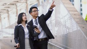 Asian young businessman use finger pointing on guide post. Close up at Asian young businessman has route guidance to pretty woman, He raised a finger pointing Stock Photography