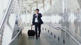Asian young businessman walking dragging suitcase with hastiness. Asian young businessman walks along the suit case with haste and checking time with a Stock Images