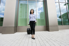 Asian young businesswoman with suitcase on sidewalk against building Stock Photo