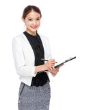 Asian young businesswoman take note on clipboard Royalty Free Stock Photos
