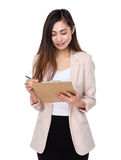 Asian young businesswoman write on clipboard Stock Images