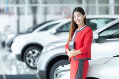Asian young car saleswoman holding calculator with a welcome dis royalty free stock photo