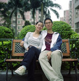 Asian young couple. Chinese young couple sitting at a bench. photo by film Royalty Free Stock Photos