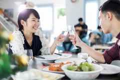 Asian young couple enjoying a romantic dinner  evening drinks wh. Ile sitting at the dinning table on the kitchen together Stock Photos
