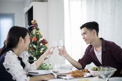 Asian young couple enjoying a romantic dinner  evening drinks wh. Ile sitting at the dinning table on the kitchen together,soft focus Royalty Free Stock Photography
