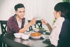 Asian young couple enjoying a romantic dinner  evening drinks wh. Ile sitting at the dinning table on the kitchen together Stock Images