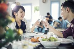 Asian young couple enjoying a romantic dinner  evening drinks wh. Ile sitting at the dinning table on the kitchen together,soft focus Royalty Free Stock Photo