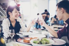 Asian young couple enjoying a romantic dinner  evening drinks wh. Ile sitting at the dinning table on the kitchen together,soft focus Stock Photo
