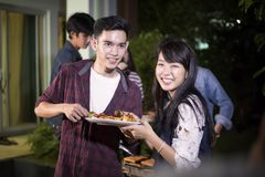 Asian young couple enjoying a romantic dinner and  group of frie. Nds having outdoor garden barbecue laughing with alcoholic beer drinks on night Stock Photography