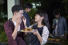 Asian young couple enjoying a romantic dinner and  group of frie. Nds having outdoor garden barbecue laughing with alcoholic beer drinks on night Royalty Free Stock Photo