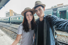 Asian young couple having fun in train station taking selfie Stock Images