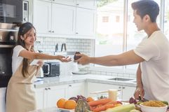 Asian young couple is looking and smiling while cooking in kitch Stock Photos