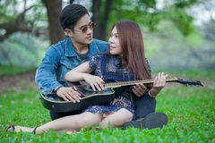 Asian young couple in love looking and embracing each other and sitting relax enjoy playing guitar in the park . boyfriend. Teaching girlfriend stock image