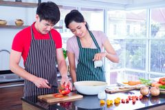 Asian young couple`s in apron, make cooking together. man are preparing to cut vegetables with knives. Woman mix salad dressing. stock photos