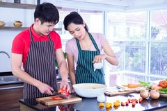 Asian young couple`s in apron, make cooking together. man are preparing to cut vegetables with knives. Woman mix salad dressing stock images