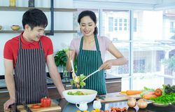 Asian young couple`s in apron, make cooking together. Woman mix salad dressing with vegetable stock photos
