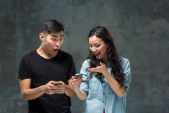 Asian young couple using cellphone, closeup portrait. Royalty Free Stock Image