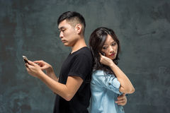Asian young couple using cellphone, closeup portrait. Stock Image