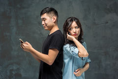 Asian young couple using cellphone, closeup portrait. Royalty Free Stock Photos