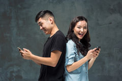 Asian young couple using cellphone, closeup portrait. Stock Images
