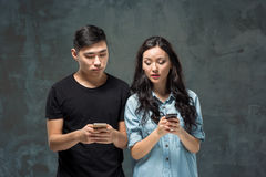 Asian young couple using cellphone, closeup portrait. Stock Photo