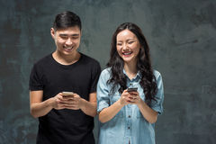 Asian young couple using cellphone, closeup portrait. Royalty Free Stock Photography