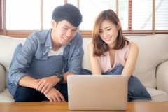 Asian young couple using laptop computer think and searching internet together, man and woman casual smiling work at home. Asian young couple using laptop royalty free stock image