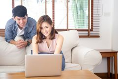 Asian young couple using laptop computer think and searching internet together, man and woman casual smiling work at home. Asian young couple using laptop stock photo