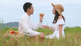 Asian young couples doing picnic in green meadow field background. Man give apple to woman to eating between flirting honeymoon in