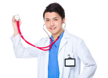 Asian young doctor holding up with stethoscope Stock Photos