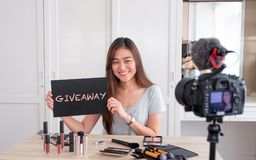 Asian young female blogger giveaway gift to fan following channel while recording vlog video with makeup cosmetic at home online. Influencer on social media royalty free stock photos