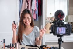 Asian young female blogger recording vlog video with makeup cosm. Etic at home online influencer on social media concept.live streaming viral royalty free stock image
