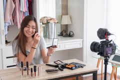 Asian young female blogger recording vlog video with makeup cosm. Etic at home online influencer on social media concept.live streaming viral royalty free stock photography