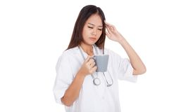 Asian young female doctor got headache with a cup of coffee Royalty Free Stock Photos