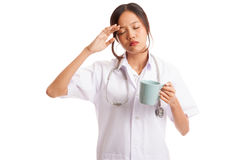 Asian young female doctor got headache with a cup of coffee Royalty Free Stock Images