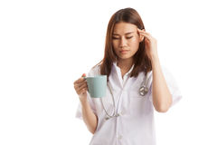 Asian young female doctor got headache with a cup of coffee. Stock Images