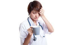 Asian young female doctor got headache with a cup of coffee. Royalty Free Stock Image