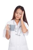Asian young female doctor got sick with a cup of coffee Royalty Free Stock Image