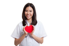 Asian young female doctor hold a red heart. Asian young female doctor hold a red heart isolated on white background royalty free stock images