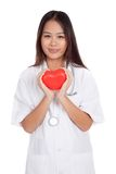 Asian young female doctor hold a red heart and smile Stock Image