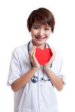 Asian young female doctor hold a red heart and smile. Asian young female doctor hold a red heart and smile isolated on white background stock photos