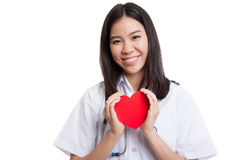 Asian young female doctor hold a red heart and smile. Asian young female doctor hold a red heart and smile isolated on white background stock photo