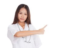 Asian young female doctor point to space on her left Royalty Free Stock Image