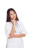 Asian young female doctor thinking looking up Stock Image