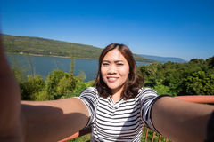 Asian young female tourist makes selfie. And smiled royalty free stock photography