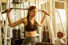 Asian young fitness woman in sportswear exercising building muscles with machine Cable Crossover in sport gym morning ligth. Slim body strength bra athlete royalty free stock photos