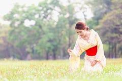 Asian young girl kimono. Asian young girl wearing a kimono in natural green grass Stock Photography